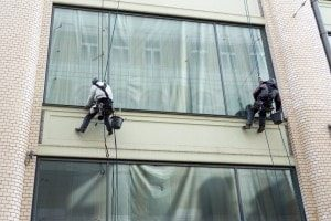 men hanging from building while cleaning windows
